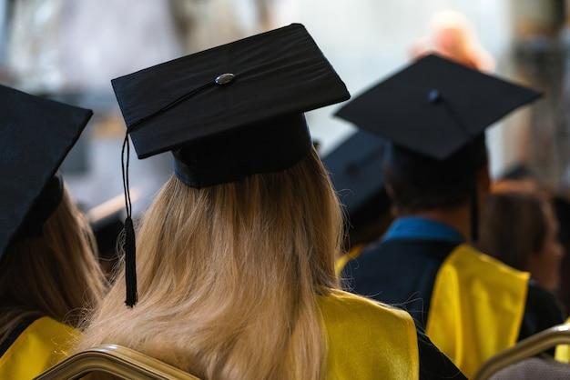 Alunos usando batas e chapéus sentados dentro de casa, esperando para receber os diplomas.