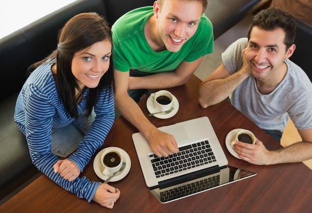 Alunos usando laptop enquanto tomando café na cafeteria