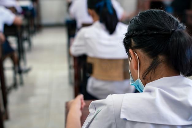Alunos usando máscara para proteger covid-19 e fazendo exame em sala de aula com estresse.