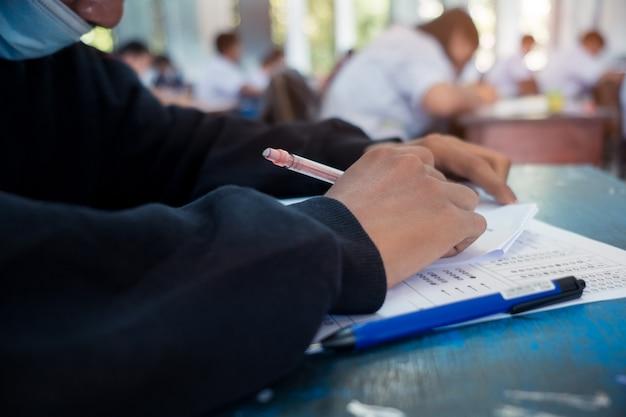Alunos usando máscara para proteger covid-19 e fazendo exame em sala de aula com estresse
