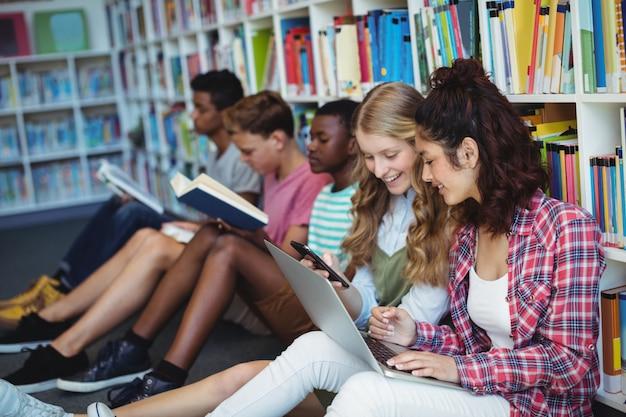 Alunos usando telefone celular e laptop na biblioteca
