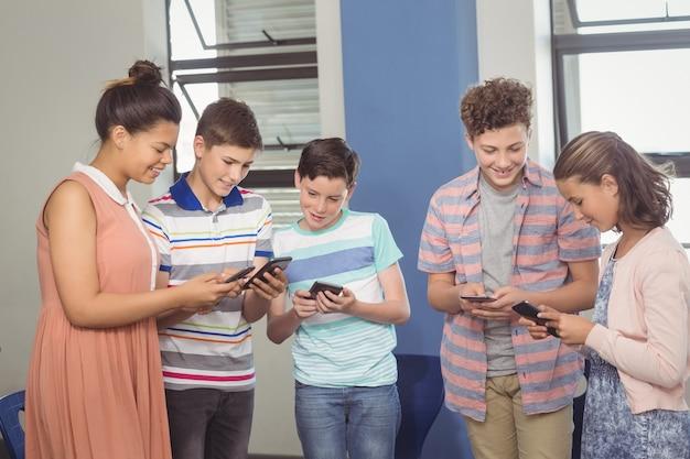 Alunos usando telefone celular na sala de aula