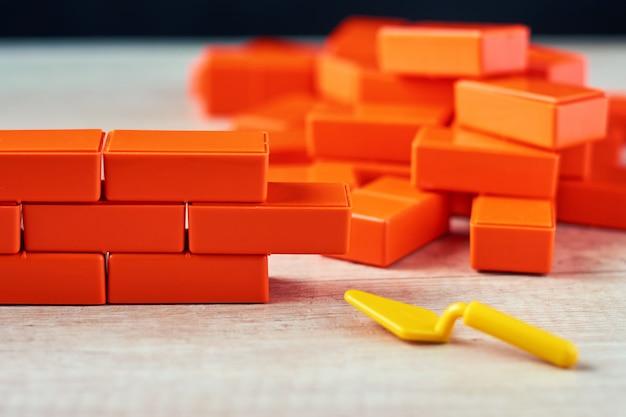 Alvenaria de blocos de brinquedo e colher de pedreiro. conceito de construção inacabada