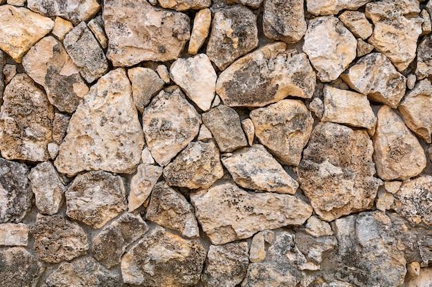 Alvenaria de calcário - a parede é feita de pedra selvagem. a superfície é decorada com material natural.