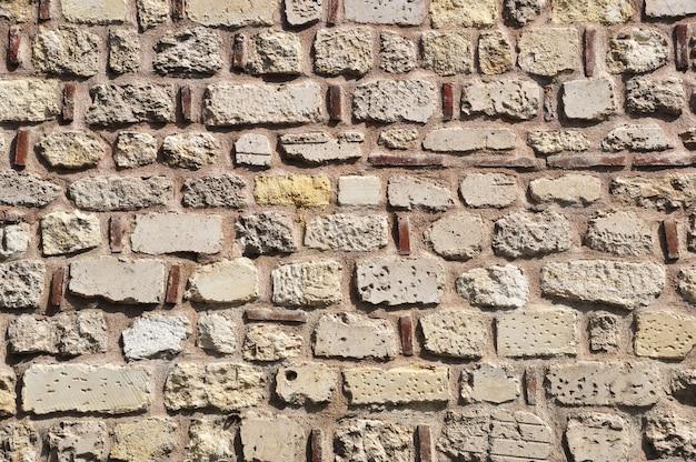 Alvenaria velha. fragmento de uma parede de tijolos. tijolos de diversos tamanhos na alvenaria das paredes.