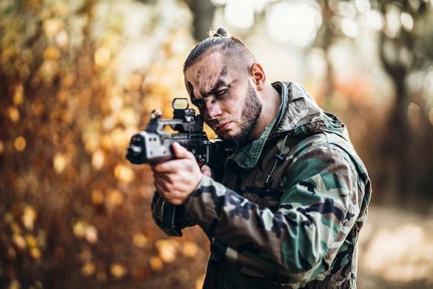 Alvo de uniforme de camuflagem e rosto pintado. segura um rifle.