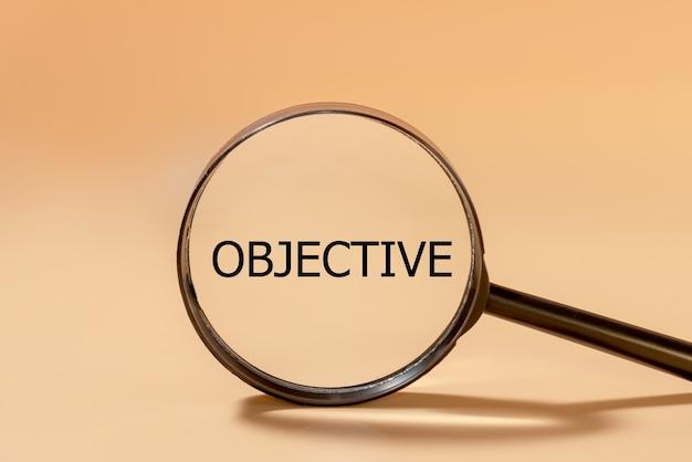 Alvo objetivo do negócio e conceito de meta, formulação de objetivo preto na lupa.