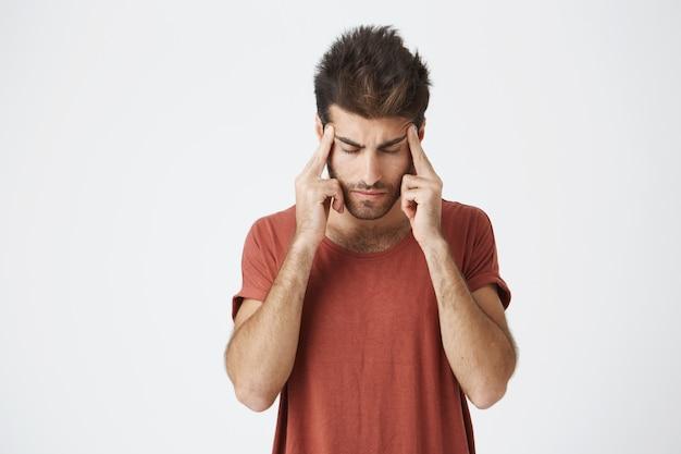 Amadureça o estudante não barbeado italiano no tshirt vermelho que guarda as mãos na testa que olha extremamente esgotada após o dia difícil no trabalho. linguagem corporal.