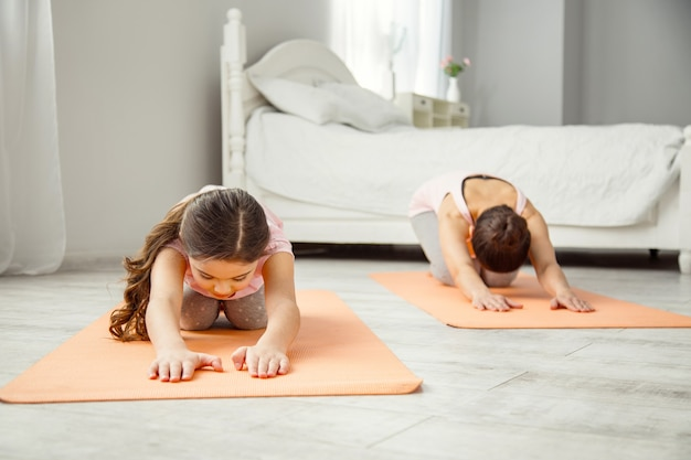 Amamos esporte. concentrada garotinha de cabelos escuros fazendo exercícios enquanto estava deitada no tapete e sua mãe se exercitando no
