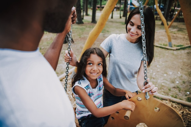 Amando a mãe e o pai balançando a filha no parque