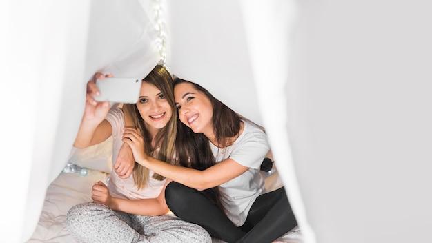 Amando amigas sentado na cama sob a cortina tendo auto-retrato no celular