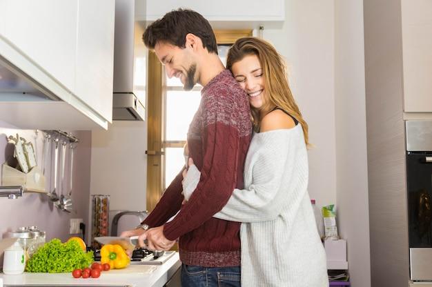 Amando e sorrindo jovem casal cozinhar comida na cozinha.