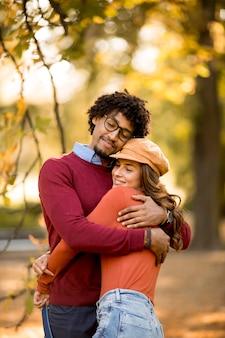 Amando, lindo casal, homem afro-americano e mulher branca, caminhando no parque de outono