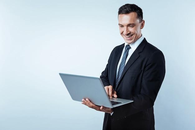 Amando meu trabalho. cintura para cima foto de um homem de mente positiva, olhando para um laptop com um largo sorriso no rosto enquanto trabalhava em um projeto e apreciava seu trabalho ao longo do fundo.