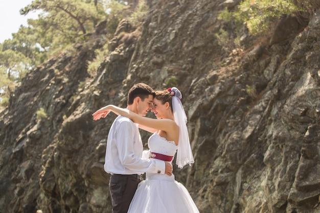 Amando o casal de noivos na praia, noiva e noivo