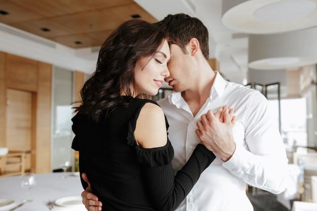 Amando o casal sorridente dançando no restaurante dentro de casa.