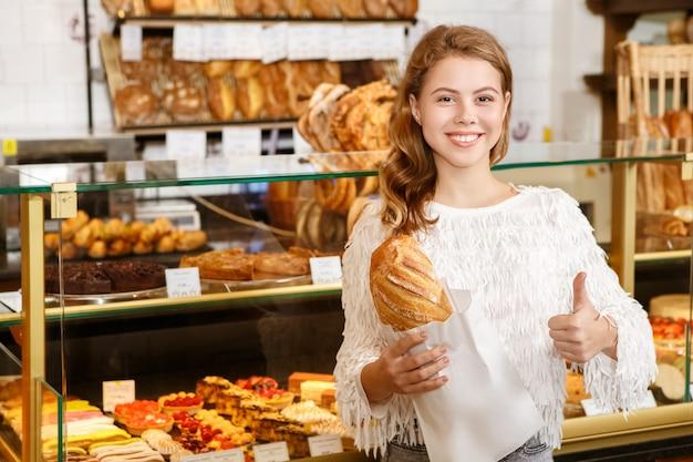 Amando o frescor. cliente feminino da padaria feliz segurando pão fresco mostrando os polegares sorrindo alegremente