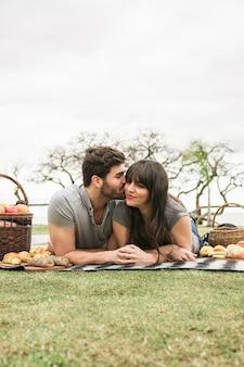 Amando o jovem casal deitado no tapete com comida assada e frutas no parque