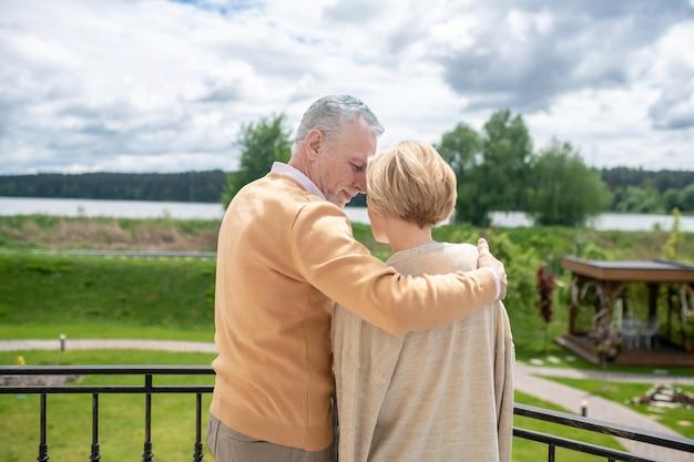 Amando, romântico atraente homem branco de meia-idade de cabelos grisalhos pressionando sua cabeça contra a testa de uma mulher loira