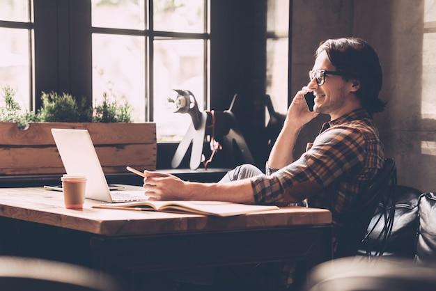 Amando seu trabalho. jovem alegre em roupas casuais, olhando para o laptop e falando ao telefone celular enquanto está sentado perto da janela no escritório criativo