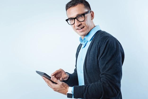 Amando todas essas tecnologias. tiro da cintura para cima de um cavalheiro maduro em traje esporte fino, olhando para a câmera com confiança enquanto vira a cabeça durante o trabalho em um computador tablet.
