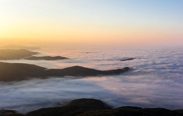 Amanhecer nas montanhas com nuvens baixas. montanhas em camadas no meio do nevoeiro. vista de cima para o vale.