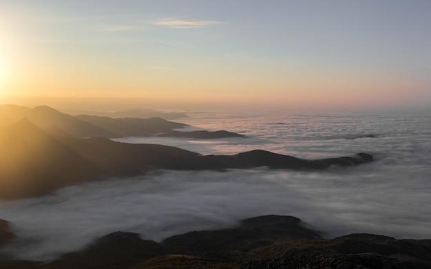 Amanhecer nas montanhas com nuvens baixas. montanhas em camadas no nevoeiro
