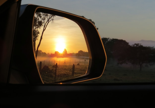 Amanhecer no espelho do carro
