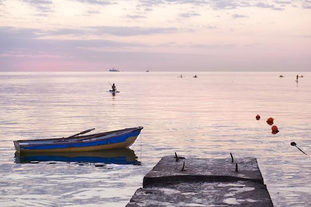 Amanhecer no mar, barco na água e uma garota em uma prancha com um remo esportes ativos e recreação