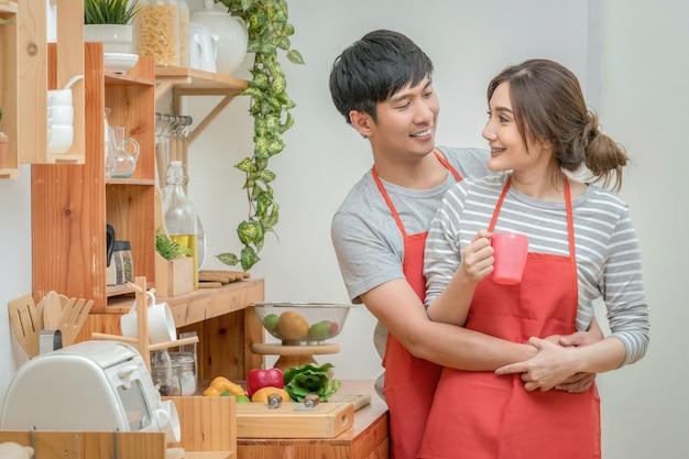 Amante asiático ou casal cozinhar e provar comida na sala da cozinha da casa moderna