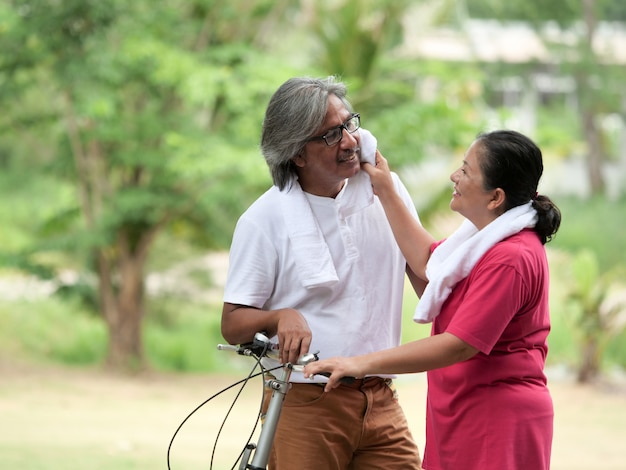 Amante casal sênior, andar de bicicleta no parque