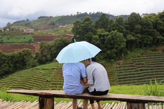 Amante com guarda-chuva sente-se na vista da montanha