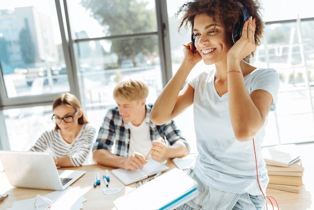 Amante da música. alegre jovem afro-americana encaracolada ouvindo música e usando fones de ouvido enquanto seus colegas de grupo estudam ao fundo
