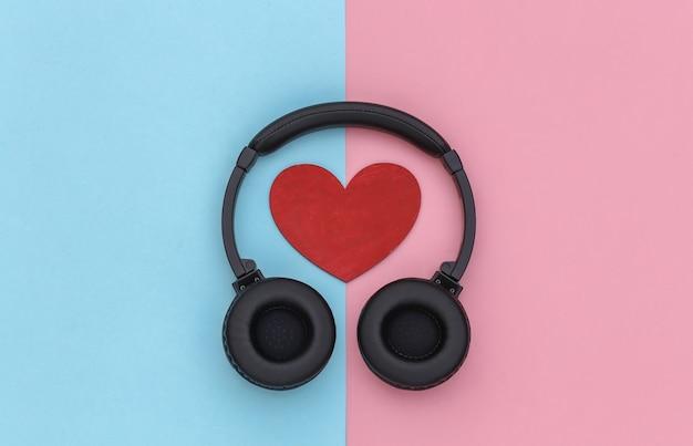 Amante da música. fones de ouvido estéreo e coração em fundo rosa pastel azul. vista do topo