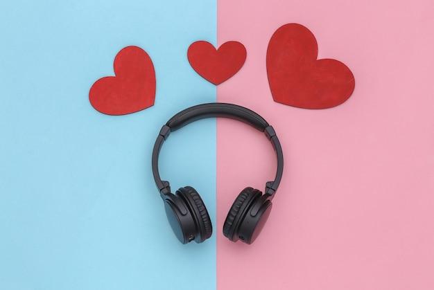 Amante da música. fones de ouvido estéreo e corações em fundo rosa pastel azul. vista do topo
