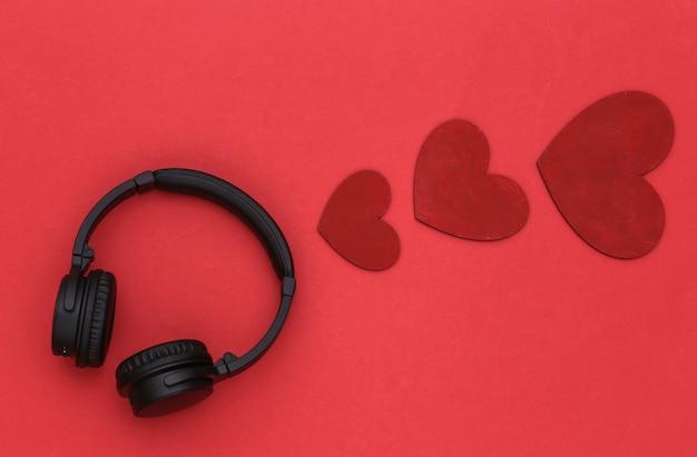 Amante da música. fones de ouvido estéreo e corações em fundo vermelho. vista do topo
