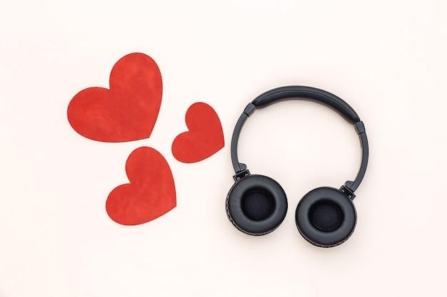 Amante da música. fones de ouvido estéreo e corações em um fundo bege. vista do topo