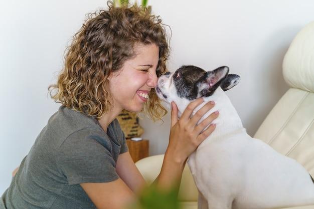 Amante de cachorro mulher com bulldog em casa. visão horizontal de mulher beijando e brincando com um cachorro dentro de casa