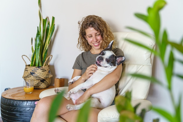 Amante de cachorro mulher com bulldog em casa. visão horizontal de mulher fazendo cócegas em cachorro isolado com plantas.