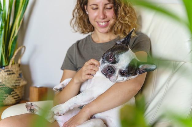 Amante de cachorro mulher com bulldog em casa. visão horizontal de uma mulher fazendo cócegas em um cachorro com plantas dentro de casa