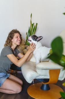 Amante de cachorro mulher com bulldog em casa. visão vertical de mulher fazendo cócegas em cachorro com plantas dentro de casa