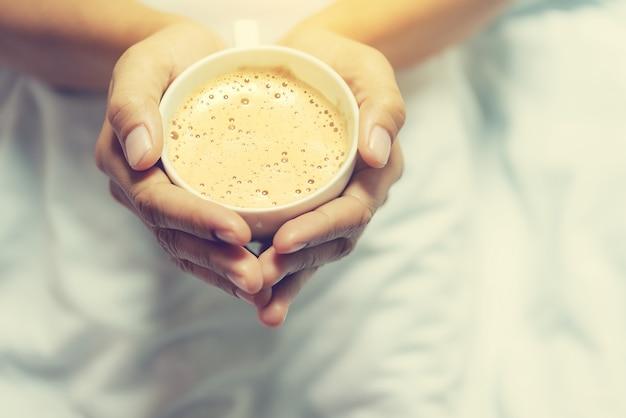 Amante de café conceito de mãos segurar café da manhã no fundo da cama borrão