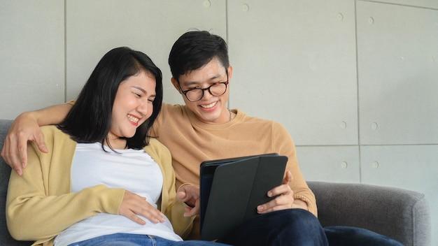 Amante de casal asiático sentados no sofá juntos usando tablet digital