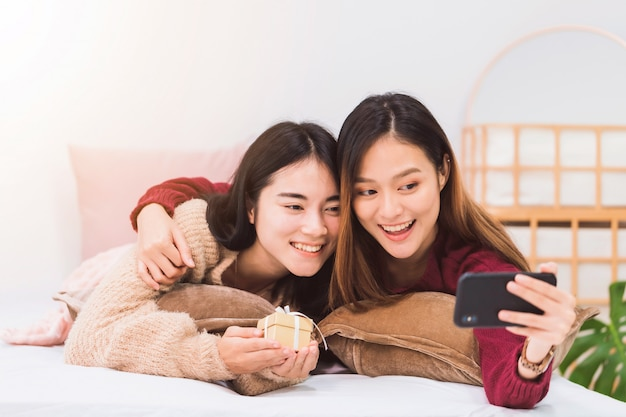 Amante de casal de lésbicas lindas mulheres asiáticas jovens dando caixa de presente e selfie com smartphone no quarto de cama em casa com rosto sorridente. conceito de sexualidade lgbt com estilo de vida feliz juntos.