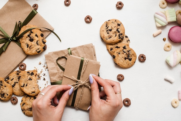 Amante de doces e presentes de natal. mulher jovem preparando pequenos presentes na mesa branca com macaroons coloridos, zéfiros e bolinhos de chocolate próximos, imagem de vista superior