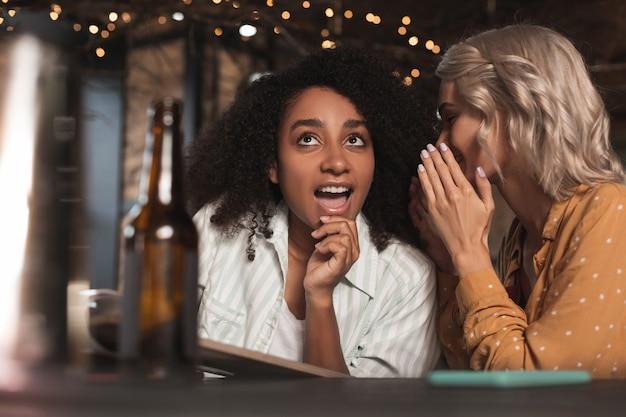 Amante de fofoca. mulher bonita e encaracolada sentada no balcão do bar ao lado da amiga, ouvindo-a sussurrar em seu ouvido e contar fofocas