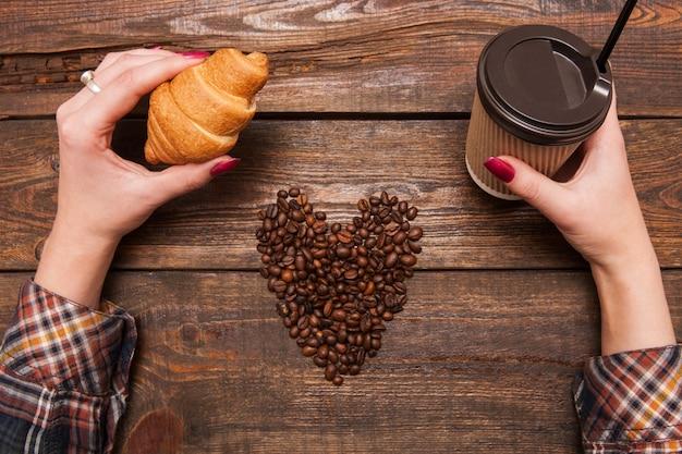 Amante do café na vista superior do café. forma de coração feita de grãos de café, mãos de mulher com bebida e sobremesa em fundo de madeira.