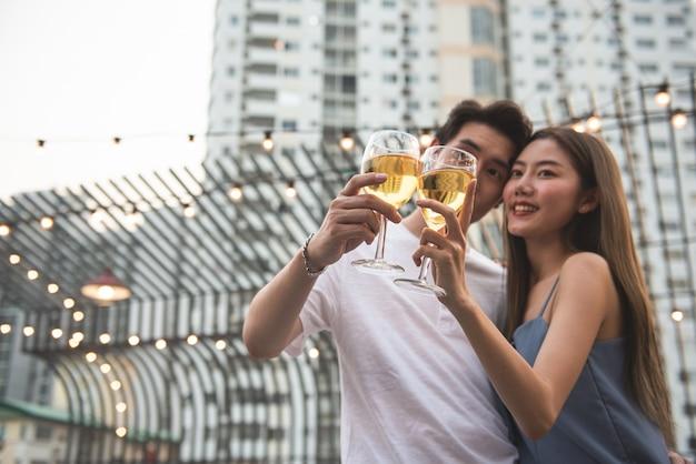 Amante do jovem casal asiático se divertir dançando e bebendo em festa à noite na mão de boate de piso no último piso, segurando a garrafa de cerveja e contato visual flertando na festa de casal. foco em dois copos de vinho.