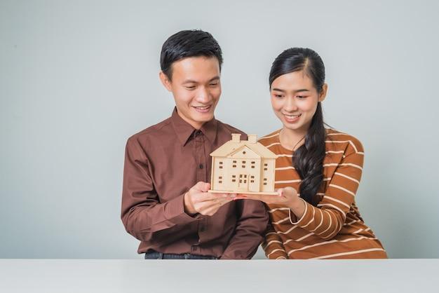 Amante do jovem casal asiático segurando a casa de madeira