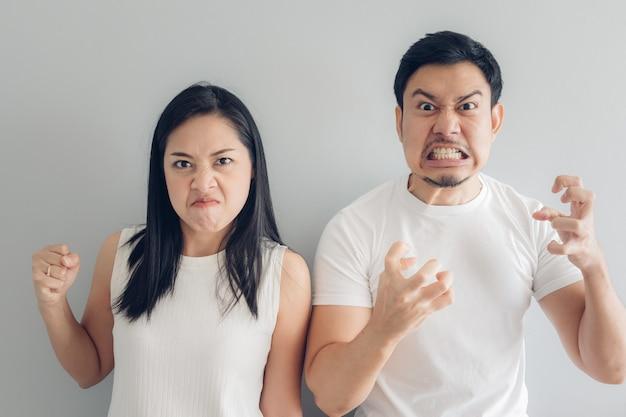 Amante irritado dos pares no t-shirt branco e no fundo cinzento.